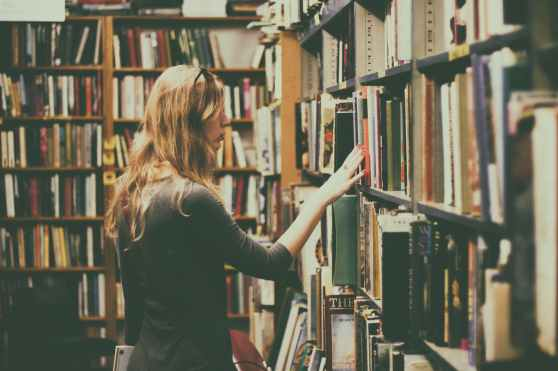 woman in black long sleeved looking for books in library
